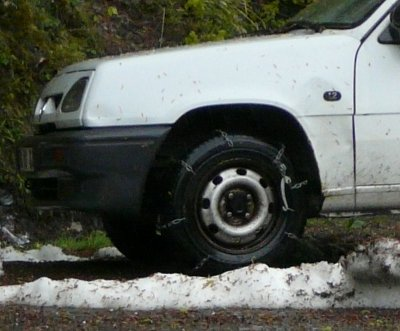 Closeup of snow chains on front wheels of French van